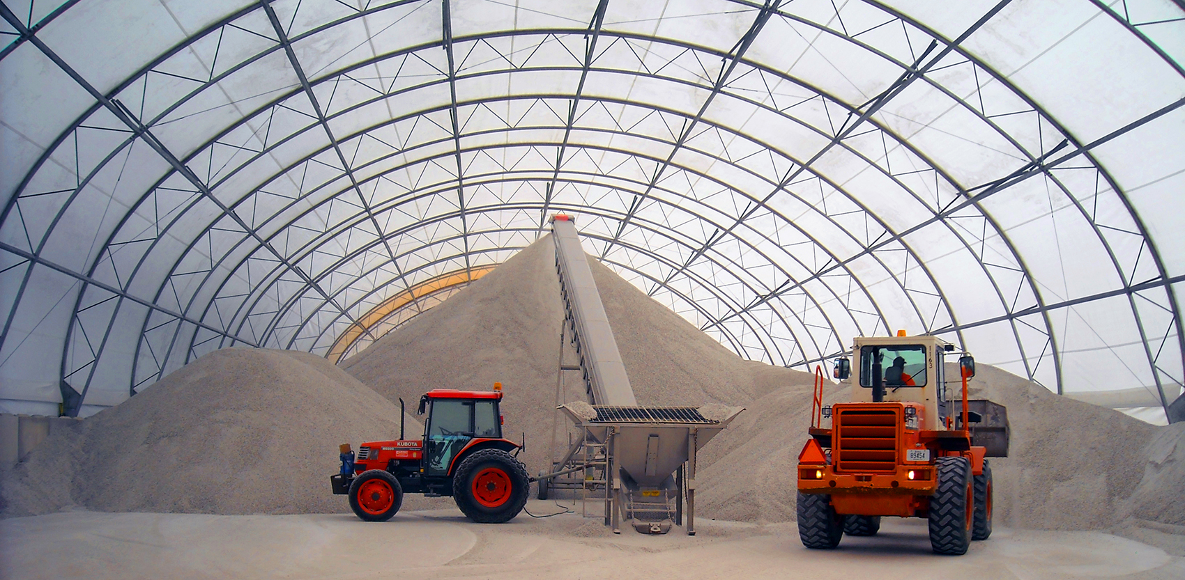 Tractors unloading salt inside a fabric-covered building